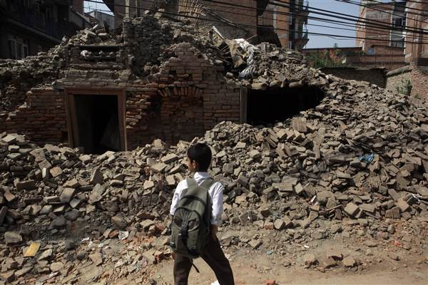 A Nepalese boy walks past a collapsed building close to his school in Kathmandu, Nepal. Photo Credit: AP